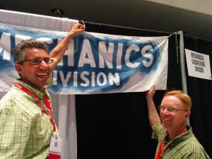 Chris Papadopoulos and Brianno Coller hanging the Mechanics Division banner.